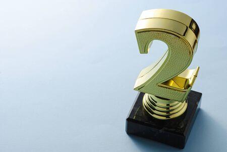 Deuxième place finaliste du trophée d'or en forme de numéro deux sur un socle vu en grand angle avec espace de copie Banque d'images