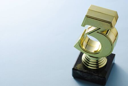Number three gold trophy for a third placed runner up in a competition or championship viewed high angle on a grey studio background with copy space