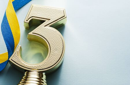 Third placed runner up textured gold number three trophy with coiled blue and yellow ribbon on a white background with copy space for a championship or competition Reklamní fotografie