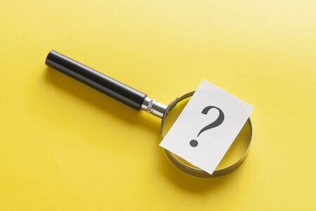 Magnifying glass covered by a question mark printed on card lying diagonally on yellow with copy space viewed from overhead in a conceptual image