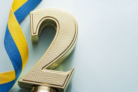 2nd placed runner up number two gold trophy for a winner in a competition, race or championship on a white background with copy space with a twirled blue and yellow ribbon