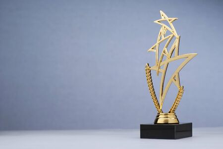 Shiny golden statue award in shape of triple star with black pedestal