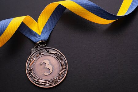Third placed runner up bronze medal for a competition on a twirled blue and gold ribbon over a black background with copy space