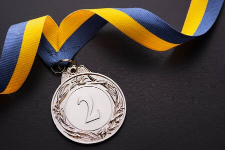 Second place runner-up silver medal on a twirled blue and gold ribbon over a dark grey background with copy space viewed from above Reklamní fotografie