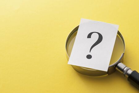 Printed question mark covering the lens of a magnifying glass over a yellow background with copy space in a conceptual image viewed close up from above Stock Photo