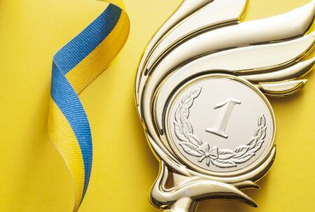 Gold Victory medal for the 1st placed winner of a championship or competition with engraved medallion over yellow with a ribbon