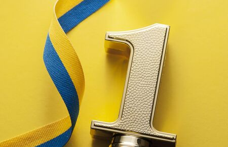 Number one gold award winner and yellow-blue ribbon on a yellow background Stok Fotoğraf