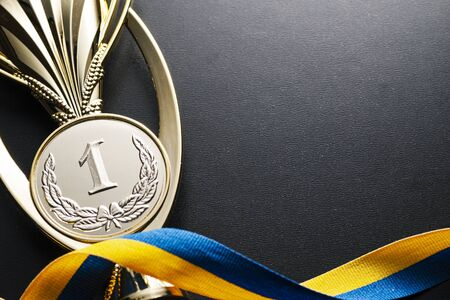 Gold winners medal for a competition, championship or race with a twirled blue and yellow ribbon on dark grey