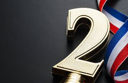 Gold number two prize or award trophy for the second placed runner-up winner in a sporting event, competition or race over grey with a twirled ribbon and copy space