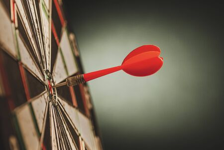 Single red dart in the bulls eye center of a target or darts board in a side view conceptual image with copy space