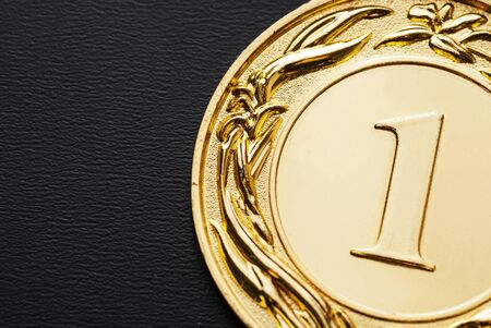Close-up of a golden medal for the number one champion as award and official recognition of the achievement