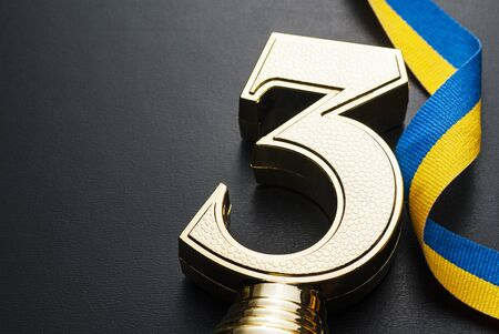 Textured gold trophy for the 3rd place runner-up in a sporting event, competition or race over grey with a blue and yellow twirled ribbon and copy space