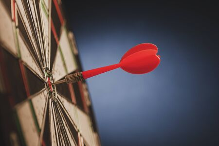 Red dart in the center of a target or darts board scoring a bulls eye in a conceptual image over blue with copy space