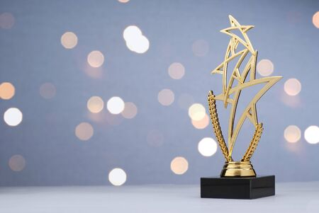 Modern championship trophy with three gold stars over a laurel wreath for the winner of a sporting event or competition against a bokeh of sparkling lights with copy space Stockfoto