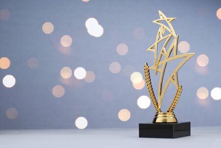 Moderne Meisterschaftstrophäe mit drei goldenen Sternen über einem Lorbeerkranz für den Sieger einer Sportveranstaltung oder eines Wettbewerbs gegen ein Bokeh aus funkelnden Lichtern mit Kopierraum Standard-Bild