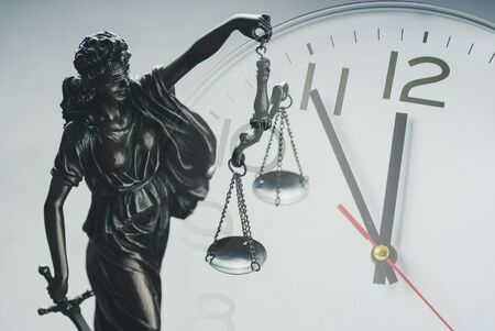 Silver statuette of Justice holding the scales of justice and law enforcement in front of a clock dial in a close up conceptual composite image