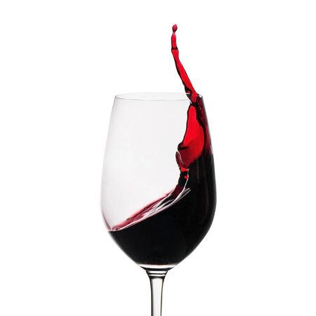 Freeze motion of red wine splashing up the side in a wineglass isolated on white with copy space