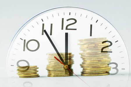 Three ascending piles of gold coins over a clock dial in a time management, viability, business efficiency and success concept Фото со стока
