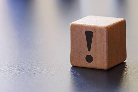 Point d'exclamation d'avertissement sur un bloc de bois pour attirer l'attention sur un fond gris avec des faisceaux de lumière et un espace de copie