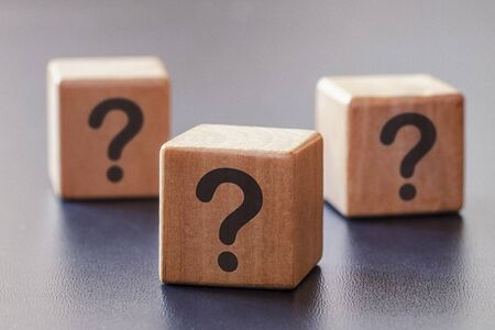 Three wooden blocks with question marks with focus to the single cube in the foreground in a conceptual image on grey