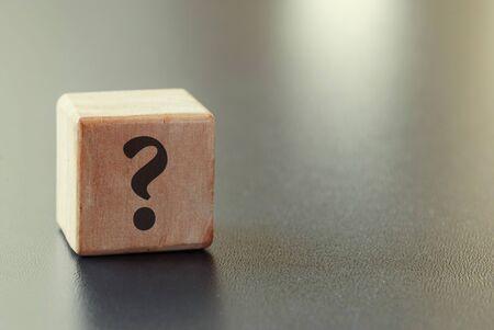 Klein houten stuk speelgoed blok met vraagteken over een grijze achtergrond met hoogtepunt en exemplaarruimte in een conceptueel beeld Stockfoto