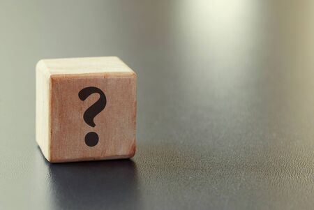Small wooden toy block with question mark over a grey background with highlight and copy space in a conceptual image Foto de archivo