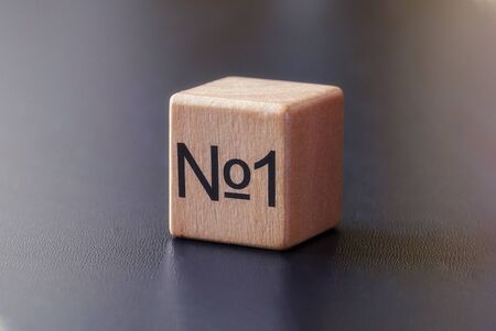 No 1 printed on the side of a wooden toy block conceptual of the best or excellence angled over a grey background