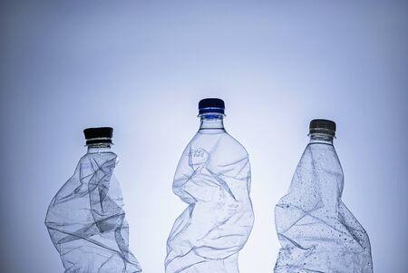 Tres botellas de plástico húmedas transparentes vacías para reciclar sobre un fondo azul en una imagen conceptual