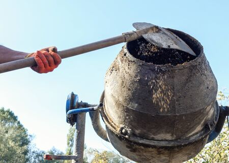 Hands of a man or builder adding components to the barrel of a cement mixer using a shovel or spade in a low angle closeup view Stock Photo