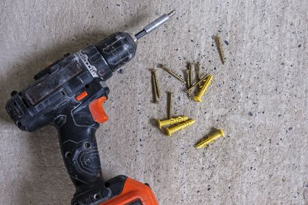 Professional automatic screwdriver and some yellow dowel nails for construction, sitting on concrete floor background and viewed from above 写真素材