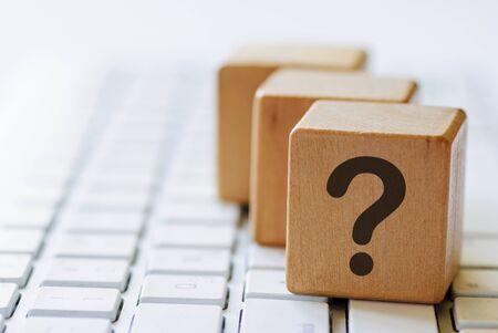 Kleine Holzwürfel mit Fragezeichen auf einer Seite, die auf der Computertastatur sitzen und in Nahaufnahme mit verschwommenem Kopierraum betrachtet werden