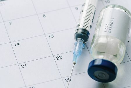 The vial with vaccine and syringe on calendar background, as a concept of vaccination season and date.