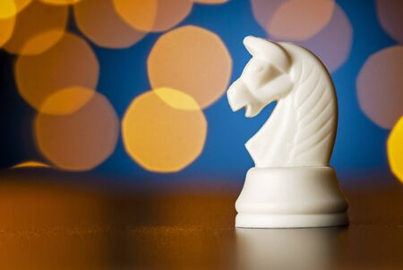 White horse chess piece on a wooden table over a colorful bokeh effect of golden light in a conceptual image Reklamní fotografie