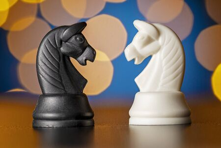 Two horse chess pieces in black and white standing on a wooden table facing each other against a colorful golden background bokeh effect Reklamní fotografie
