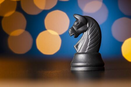 black horse chess piece on a wooden table over a colorful bokeh effect of golden light in a conceptual image