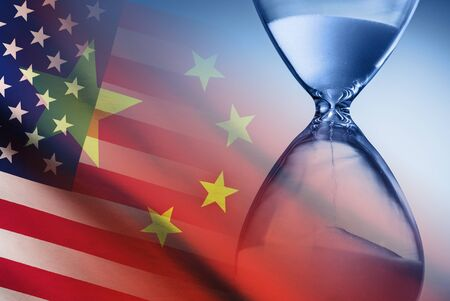 Hourglass over the flags of America and China 免版税图像