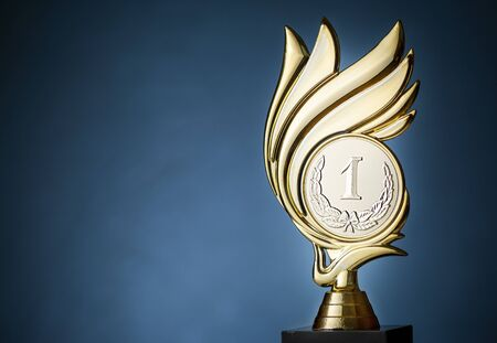 Gold flame style championship trophy for the first place winner over a blue background with copy space Stock Photo