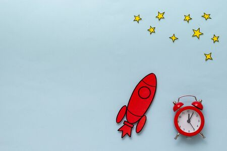 Red cartoon rocket with alarm clock and yellow stars in a conceptual image on a blue background with copy space Stok Fotoğraf