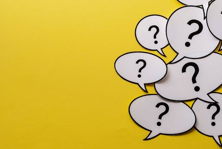 Multiple question marks in speech bubbles forming side border o a bright yellow background with copy space