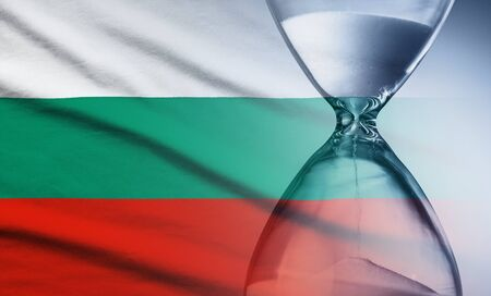 Flag of Bulgaria with superimposed hourglass with running sand conceptual of deadlines, countdown, passing time, urgency, crisis and time management