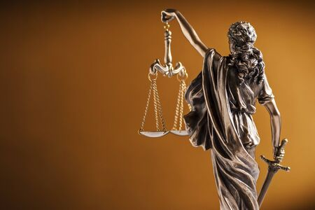 Rear view of a small statue of Lady Justice holding up the scales of law and order and carrying a sword over a graduated brown background with copy space