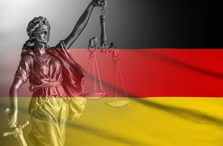 Flag of Germany with a statue of Justice holding aloft scales and a sword in a composite image conceptual of law and order