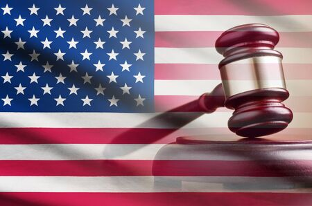 Legal gavel on its plinth over a flag of the USA in a conceptual composite image Banco de Imagens
