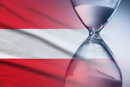 Flag of Austria with superimposed hourglass with running sand conceptual of deadlines, countdown, passing time, urgency, crisis and time management 写真素材