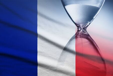 Flag of France with superimposed hourglass conceptual of deadlines