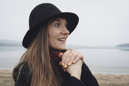 Side view portrait of a woman wearing a black hat