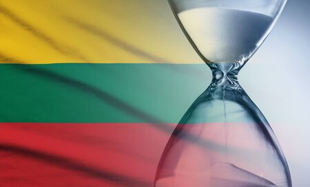 Hourglass with running sand over the flag of the Lithuania in a concept of urgency, countdown , deadlines and time management
