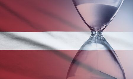 Hourglass with running sand over the flag of the Latvia in a concept of urgency, countdown , deadlines and time management Stockfoto