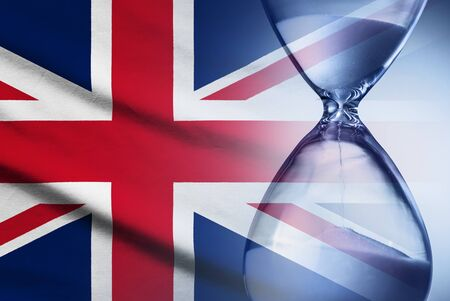 Hourglass with sand running through measuring passing time to a deadline with the British Union Jack flag in a conceptual image 版權商用圖片
