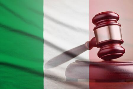 Legal gavel on its plinth over a flag of the Italy in a conceptual composite image Banque d'images